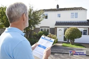 roofer holds inspection checklist in front of house