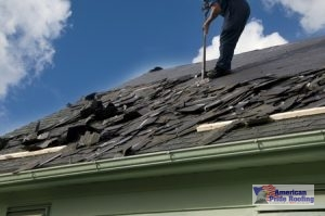 roofer sweeps off removed shingles for new replacement