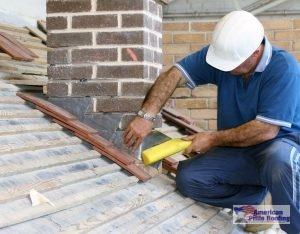 roofer caulks roof flashing