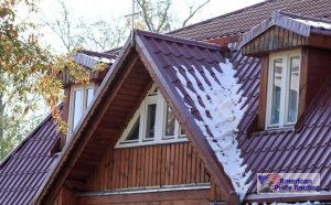 snow on sloped red metal roof