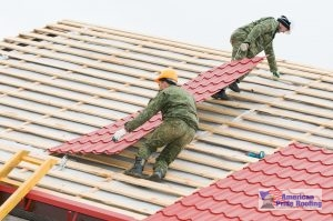 workers installing red metal panels on roof