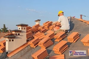 roofer sits on roof with tiles watiging to be installed